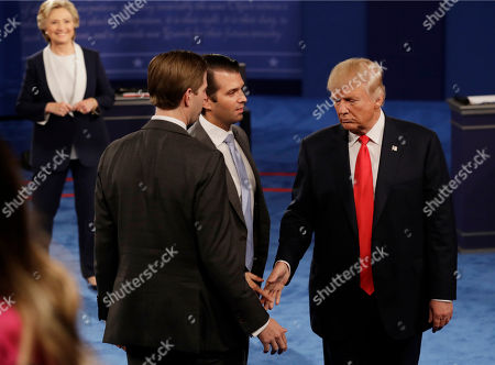 Republican presidential nominee Donald Trump shakes hands with his sons Eric, left, and Donald Trump Jr. following the second presidential debate with Democratic presidential nominee Hillary Clinton at Washington University in St. Louis