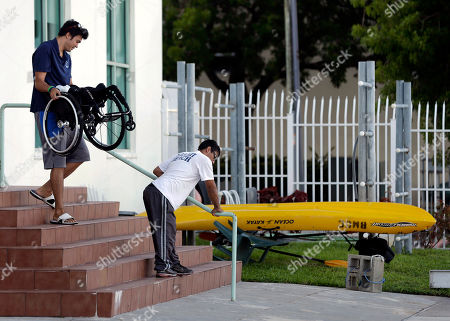 Juan Carlos Gil, Justin Kallman Juan Carlos Gil, right, uses a railing to get down stairs as his coach Justin Kallman carries his wheelchair as they prepare for a rowing training session at the Miami Beach Rowing Club in Miami Beach, Fla. According to head coach Bob Wright, rowing is a sport that accommodates disabilities very well. Although Gil is unable to use his legs in the rowing stroke, he can compensate by conditioning to strengthen his core in his shoulders, arms and back