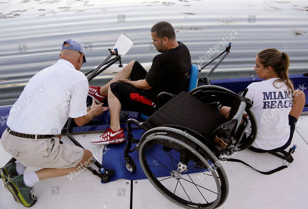 Louis Amaro, Bob Wright, Davian Campbell Louis Amaro, center, of Miami Gardens, Fla., is helped out of his wheelchair and into a rowing boat by head coach Bob Wright, left, at the Miami Beach Rowing Club in Miami Beach, Fla. Amaro, who is a paraplegic, participates in the adaptive rowing program for people with disabilities at the rowing club. At right is volunteer Daviana Campbell