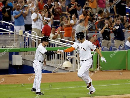 Giancarlo Stanton, Brett Butler Miami Marlins' Giancarlo Stanton, right, is met by third base coach Brett Butler, left, as he rounds third base in the third inning after hitting his second home run during a baseball game against the St. Louis Cardinals, in Miami
