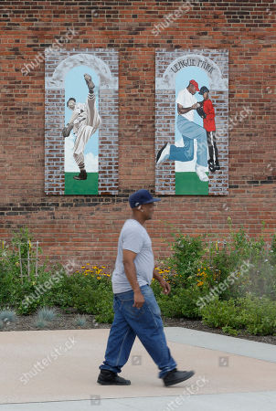 David Rouse walks past paintings on the original wall at League Park in Cleveland. The city of Cleveland has invested $6.3 million in restoring the old site of League Park, a historic site where the Cleveland Indians clinched its 1920 World Series title, Babe Ruth hit his 500th home run and where Joe DiMaggio extended his hitting streak to 56 games