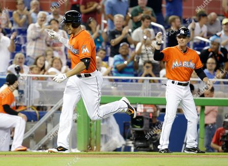 Giancarlo Stanton, Brett Butler Miami Marlins' Giancarlo Stanton, left, rounds third base after hitting a three-run home run in the first inning during a baseball game against the Arizona Diamondbacks, Sunday, Aug.17, 2014, in Miami. At right is Miami Marlins third base coach Brett Butler