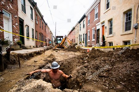 Stock Picture of Construction worker Vinny Chase climbs out of a pit during a sewer and water line project, in Philadelphia