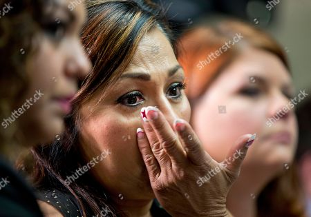 "Rosie Cortinas, Monica Coronado, Laura Christian Rosie Cortinas, center, from Homedale, Idaho, mother of Amador Cortinas, with her daughter Monica Coronado, left, and Laura Christian, of Harwood, Md., birth mother of Amber Marie Rose, right, wipes away tears as she listens to Kenneth Feinberg, the independent claims administrator for the GM Ignition Compensation Program, announces the details of the program, including eligibility, scope, rules for the program, and timing of submitting claims, during a news conference at the National Press Club in Washington, . Amador Cortinas, was 23 years old, when he died of a vehicular accident allegedly involving a ""defective GM vehicle,"" Rosie Cortinas claimed"