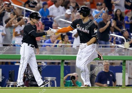Brett Butler, Giancarlo Stanton Miami Marlins' Giancarlo Stanton, right, is congratulated by third base coach Brett Butler after Stanton hit a solo home run during the ninth inning of a baseball game against the San Francisco Giants, in Miami. The Giants defeated the Marlins 5-3