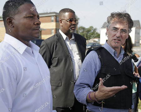 """Eric J. Kellogg, Sean Howard, Tom Dart Harvey Mayor Eric J. Kellogg, left, and city spokesman Sean Howard, second from left, stand by as Cook County Sheriff Tom Dart speaks at a news conference after a hostage standoff in the Chicago's south suburb of Harvey, Ill. A published report says the mayor of the financially struggling Harvey, directed a federal grant be used to buy a $51,000 SUV for his own use while the money was intended to buy two new police cars for Harvey, where officials said they didn't have enough cruisers to patrol the streets. Howard also says Kellogg is a part-time police officer in a neighboring department and the Chevy Tahoe is """"used to deter crime"""