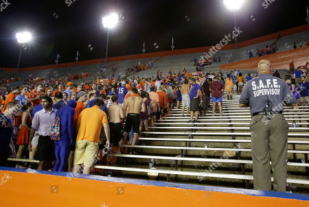 Football fans exit Ben Hill Griffin Stadium after an NCAA college football game between Florida and Idaho was cancelled due to weather conditions in Gainesville, Fla