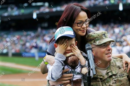 "Stock Photo of Petty Officer 1st Class Rob Patterson, right, of the U.S. Naval Reserve, poses for a photo with his wife, Ungsana Patterson, and their son, Roger Patterson, 6, left, after Rob surprised Roger as the child was getting ready to say the traditional ""Play Ball"" at the start of a baseball game between the Seattle Mariners and the Cleveland Indians, in Seattle. Rob Patterson has been deployed for more than seven months in Afghanistan and was originally scheduled to return in July"