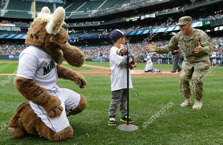 "Stock Image of Petty Officer 1st Class Rob Patterson, right, of the U.S. Naval Reserve, surprises his son Roger Patterson, 6, center, as Roger gets ready to say the traditional ""Play Ball"" at the start of a baseball game between the Seattle Mariners and the Cleveland Indians, in Seattle. Rob Patterson has been deployed for more than seven months in Afghanistan and was originally scheduled to return in July"