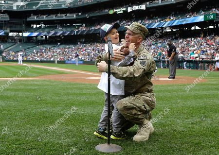 "Petty Officer 1st Class Rob Patterson, right, of the U.S. Naval Reserve, hugs his son, Roger Patterson, 6, left, after Patterson surprised his son as Roger was getting ready to say the traditional ""Play Ball"" at the start of a baseball game between the Seattle Mariners and the Cleveland Indians, in Seattle. Rob Patterson has been deployed for more than seven months in Afghanistan and was originally scheduled to return in July"