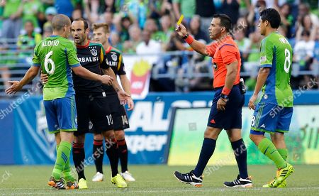 Landon Donovan Los Angeles Galaxy's Landon Donovan, second from left, is booked with a yellow card by referee Hilario Grajeda, second from right, after Donovan fouled Seattle Sounders' Osvaldo Alonso, left, in the first half of an MLS soccer match, in Seattle