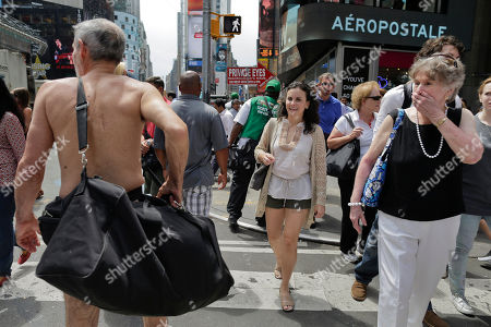 Pedestrians react as George Davis, left, walks nude through Times Square, in New York. Davis, a candidate for the San Francisco Board of Supervisors, gave a speech in the nude speaking out against a 2013 San Francisco public nudity ban that was introduced by his opponent, Scott Wiener, saying nudity is a freedom of expression