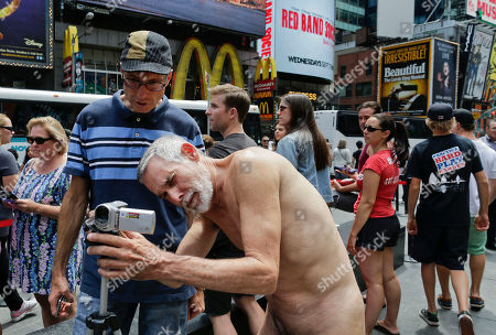 George Davis, a candidate for the San Francisco Board of Supervisors, checks his video camera after making a speech in the nude on Times Square, in New York. Davis spoke out against a 2013 San Francisco public nudity ban that was introduced by his opponent, Scott Wiener, saying nudity is a freedom of expression