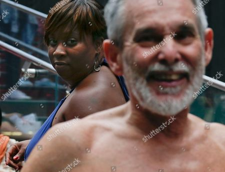 A visitor to Times Square looks on as San Francisco Board of Supervisors candidate George Davis gives a speech in the nude, in New York. Davis spoke out against a 2013 San Francisco public nudity ban that was introduced by his opponent, Scott Wiener, saying nudity is a freedom of expression