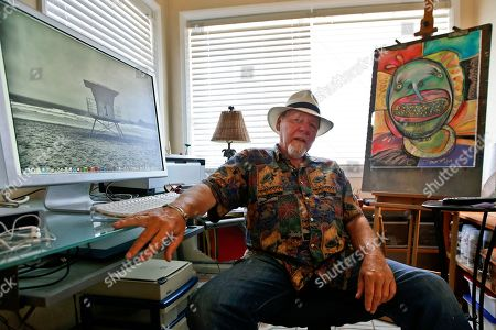 """Michael Gross Artist Michael Gross sits in his studio between one of his paintings and one of his photos on his computer screen in Oceanside, Calif. Gross, an artist who created two of the most distinctive pop culture images of the 20th century, died . He was 70. Gross first gained wide attention in 1973 for the National Lampoon cover of a dog with a gun to its head and the words, """"If You Don't Buy This Magazine, We'll Kill This Dog."""" A decade later, he created the enduring symbol of a confused looking ghost in the middle of a slashed red circle for the film """"Ghostbusters"""