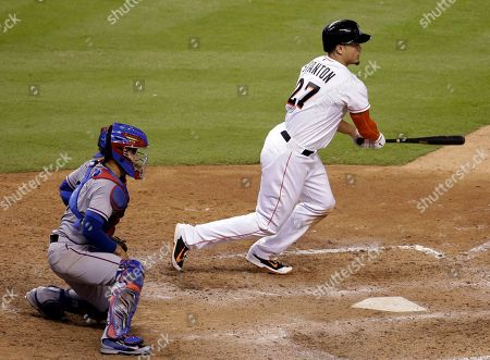 Giancarlo Stanton, Robinson Chirinos Miami Marlins' Giancarlo Stanton watches his single that scored Jeff Baker in the 10th inning for the winning run, in front of Texas Rangers catcher Robinson Chirinos, left, during a baseball game, in Miami. The Marlins defeated the Rangers 4-3 in 10 innings