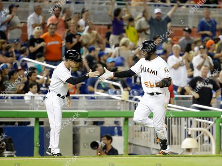Marcell Ozuna, Brett Butler Miami Marlins' Marcell Ozuna, right, is met by third base coach Brett Butler, left, as he rounds third base after hitting a solo home run during a baseball game, in Miami