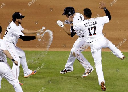 Giancarlo Stanton, Henderson Alvarez, Donovan Solano Miami Marlins' Giancarlo Stanton, center, is sprayed with water by Henderson Alvarez (37) after hitting a single to score Jeff Baker in the 10th inning for the game-winning run during a baseball game, in Miami. The Marlins defeated the Texas Rangers 4-3. At right is Donovan Solano