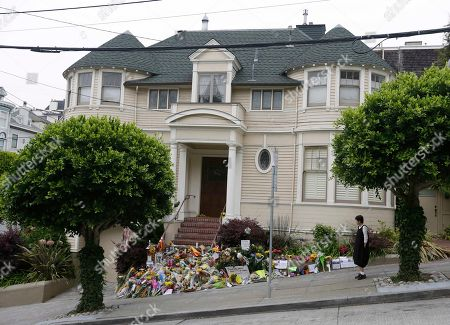 """A woman stops to look at a makeshift memorial for actor Robin Williams outside a home which was used in the filming of the movie """"Mrs. Doubtfire"""", in San Francisco. People continue to stop and look at the memorial on the steps of the Pacific Heights home. Williams was in the early stages of Parkinson's disease at the time of his death, his wife said Thursday. In a statement, Susan Schneider said that Williams, 63, was struggling with depression, anxiety and the Parkinson's diagnosis when he died Monday in his Northern California home. Authorities said he committed suicide"""