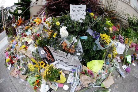 """Shown is a makeshift memorial for actor Robin Williams outside a home which was used in the filming of the movie """"Mrs. Doubtfire"""", in San Francisco. People continue to stop and look at the memorial on the steps of the Pacific Heights home. Williams was in the early stages of Parkinson's disease at the time of his death, his wife said Thursday. In a statement, Susan Schneider said that Williams, 63, was struggling with depression, anxiety and the Parkinson's diagnosis when he died Monday in his Northern California home. Authorities said he committed suicide"""