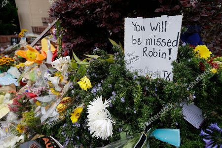 """A makeshift memorial for actor Robin Wlliiams is shown outside a home which was used in the filming of the movie """"Mrs. Doubtfire"""", in San Francisco. People continue to stop and look at the memorial on the steps of the Pacific Heights home. Williams was in the early stages of Parkinson's disease at the time of his death, his wife said Thursday. In a statement, Susan Schneider said that Williams, 63, was struggling with depression, anxiety and the Parkinson's diagnosis when he died Monday in his Northern California home. Authorities said he committed suicide"""