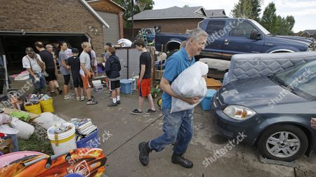 Family and friends remove wet belongings from a home after heavy rains overnight flooded the home, in West Jordan, Utah. Seventeen homes and basements were flooded in West Jordan early Wednesday. West Jordan Deputy Chief Reed Scharman told KSL that the city received almost an inch of water in an hour, filling storm drains and backing up a canal. Residents started calling emergency crews for help around 4:30 a.m