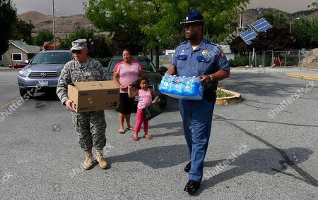 John Batiste, Bret Daugherty Washington State Patrol Chief John Batiste, right, and Major General Bret Daugherty, left, carry water and food donated by Yessica Escobar and her daughter Maylin Villanueva, 5, center, at a Red Cross shelter for people displaced by wildfires in Chelan, Wash., . Batiste and Daugherty were accompanying Gov. Jay Inslee on a tour of areas affected the fires