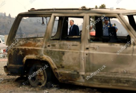 Jay Inslee Washington Gov. Jay Inslee, center, and Washington State Patrol Chief John Batiste, right, are seen through the windows of a burned out car as they visit the site of a home that was destroyed by wildfires near the Alta Lake Golf Course in Pateros, Wash., . The Governor was in the area to access needs and damage after wildfires swept through the region overnight