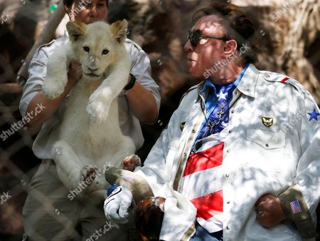 Roy Horn looks at a white lion cub during an event to welcome three white lion cubs to Siegfried & Roy's Secret Garden and Dolphin Habitat, in Las Vegas. The three white lion cubs, born in South Africa, are scheduled to be available for public viewing Friday