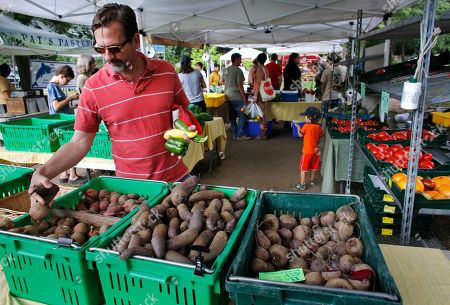 FILE - In this July 30, 2014 photo, David Mann, of Pawtucket, R.I., shops for vegetables at the Wishing Stone Farm stand at a farmers market, in Providence, R.I. The Commerce Department reports on wholesale stockpiles and sales in August on