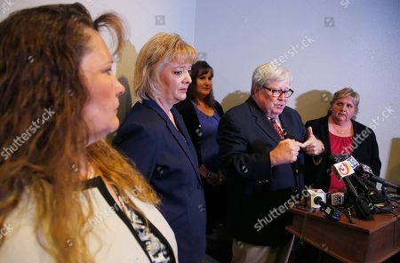 Stock Picture of Deborah Harper, Tracey Everitt, Michelle Parker, Jana Leineweber, Terry Woods Joined by their lawyer Terrence Woods, second from right, speaks on behalf of the five senior Arizona child welfare employees, including Michelle Parker, left, Tracey Everitt, second from left, Jana Leineweber, third from left, and Deborah Harper who were fired last month for their role in the closure of more than 6,500 Arizona child abuse and neglect cases at a news conference, in Phoenix. For the first time since their firings they speak out to explain and defend their actions