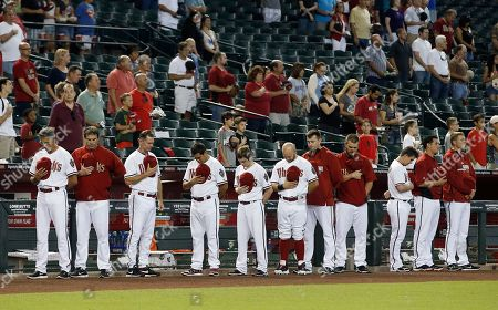 Arizona Diamondbacks players and coaches pause for a moment of silence on the announcement of the death of former MLB player Bob Welch prior to a baseball game against the Houston Astros, in Phoenix