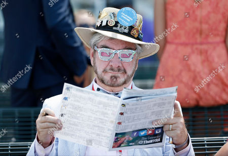 Charles Clarke III reads a program at Belmont Park before the Belmont Stakes horse race, in Elmont, N.Y