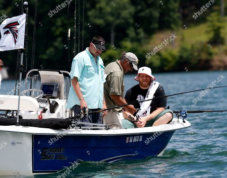 Purple Heart recipient Sgt. Jason Ulin, of Savannah, Ga., left, fishes with Atlanta Falcons' offensive tackle Sam Baker, right, and fishing guide John Mantovani during the team's annual 'Fishing With the Falcons' event with wounded veterans on Lake Lanier in Buford, Ga. . The Falcons host the annual out outing to thank wounded veterans. Ulin served two tours in Afghanistan