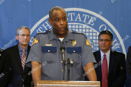 Washington state Patrol Chief John Batiste, center, speaks to the media about public awareness and safety efforts the state is making in advance of the start of retail sales of recreational marijuana, on in Olympia, Wash. Batiste says troopers are trained to recognize stoned drivers