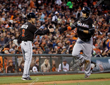 Giancarlo Stanton Miami Marlins' Giancarlo Stanton, right, shakes hands with third base coach Brett Butler after his solo home run against the San Francisco Giants during the seventh inning of a baseball game, in San Francisco