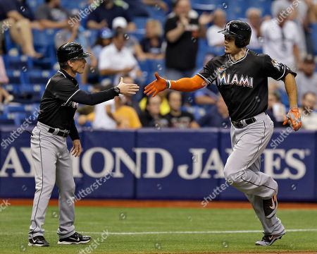 Giancarlo Stanton, Brett Butler Miami Marlins' Giancarlo Stanton, right, reaches out to shake hands with third base coach Brett Butler after his two-run home run off Tampa Bay Rays relief pitcher Brad Boxberger during the seventh inning of an interleague baseball game, in St. Petersburg, Fla. Marlins' Donovan Solano also scored on the hit