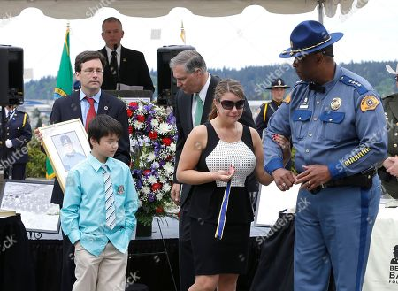 Alissa O'Connell, John Batiste Washington State Patrol Chief John Batiste, right, escorts Alissa O'Connell, second from right, and her son Kian, 8, lower left, after O'Connell was given a state law enforcement medal of honor by Gov. Jay Inslee, third from right, and Attorney General Bob Ferguson, upper left, on behalf of her husband, Trooper Sean O'Connell Jr., lower right, who was killed May 31, 2013, in a motorcycle accident while he was helping with a traffic detour around the collapsed Skagit River Bridge, during the annual law enforcement medal of honor ceremony, at the Capitol in Olympia, Wash