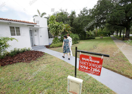 Mary Tuttle, Nancy Dowson Real estate broker Nancy Dowson, center right, with Keller Williams Realty, shows a house to prospective buyer Mary Tuttle, center, in Miami Shores, Fla. Freddie Mac releases weekly mortgage rates on Thursday, June 12, 2014