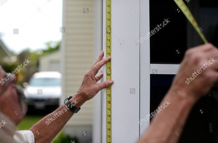 Bob Parsons In this picture, homeowner Bob Parsons measures how high he plans to raise his house in Norfolk, Va. Despite frequent flooding in the neighborhood, Parsons intends to stay put after the house is raised