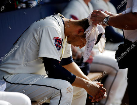 Andrelton Simmons, Jim Lovell Atlanta Braves' Andrelton Simmons has a wet towel draped over his head by trainer Jim Lovell as he sits in the dugout in the fourth inning of a baseball game against the Colorado Rockies, in Atlanta