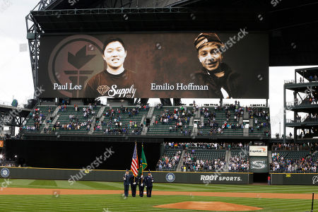 The Seattle Mariners pay tribute, to Paul Lee, left, who was killed by a gunman, June 5, 2014, at Seattle Pacific University in Seattle, and Emilio Hoffman, right, a freshman, who was killed earlier in the day Tuesday by a gunman at Reynolds High School in Troutdale, Ore. The display took place before a baseball game between the Seattle Mariners and the New York Yankees