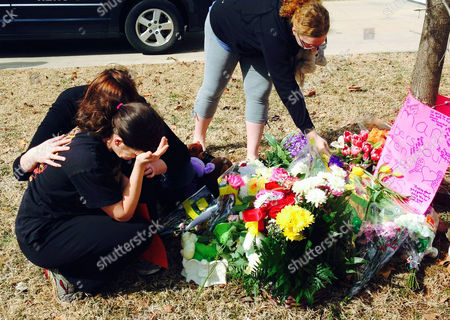 Stacey Barfield, mother of Hailey Owens, foreground left, is consoled by Sara Wells, as family member Teri Nord, right, arranges flowers left by well wishers near the site where the 10-year-old girl was abducted just blocks from her Springfield, Mo., home. Prosecutors have charged Craig Michael Wood with first-degree murder, kidnapping and armed criminal action in their girls death. Prosecutors says the fourth-grader's body was found stuffed in two trash bags inside plastic storage containers in the basement of Wood's Springfield home. She had been shot in the head