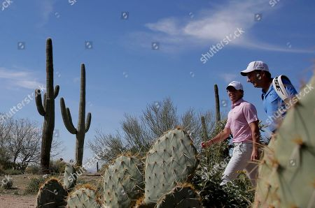 Dave Renwick, Rory McIlroy Rory McIlroy, left, walks off the 17th tee with his caddie, JP Fitzgerald, during a practice round for the Match Play Championship golf tournament, in Marana, Ariz