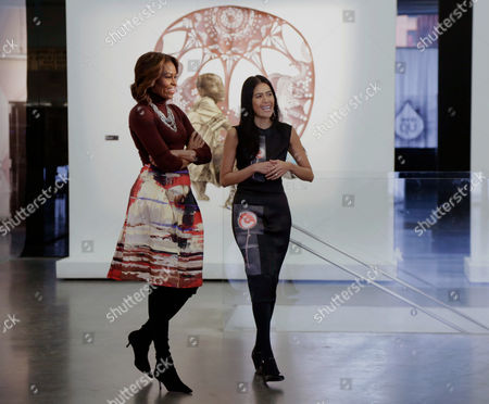 "Stock Photo of Michelle Obama, Rose Cameron First lady Michelle Obama is escorted by Rose Cameron, CEO and founder of WAT-AAH!, a line of bottled water targeted to kids and teens, as they view the ""Taking Back the Streets"" art exhibit at the New Museum, in New York"