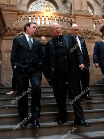 Michael Cusick, Timothy Dolan Cardinal Timothy Dolan, right, walks down the Million Dollar Staircase at the Capitol with Assemblyman Michael Cusick, D-Staten Island,, in Albany, N.Y. Dolan and bishops from around the state are advocating for a new tax credit for charitable donations made for educational purposes. The legislation would eventually add up to $300 million a year for education, with half going to public school programs and half going to scholarships for students who attend private schools