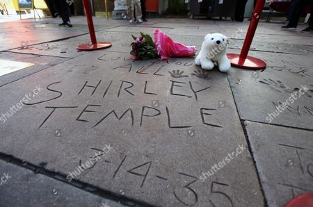 Flowers and a stuffed animal are left at the hand and foot prints for Shirley Temple Black at the TCL Chinese Theatre in the Hollywood section of Los Angeles on . Temple, who died Monday night at 85, sang, danced, sobbed and grinned her way into the hearts of Depression-era moviegoers and remains the ultimate child star decades later