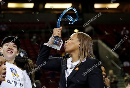 Cynthia Cooper Southern California head coach Cynthia Cooper kisses the championship trophy as she stands with her team on an award podium after they beat Oregon State to win the Pac-12 NCAA college championship basketball game, in Seattle. USC won 71-62