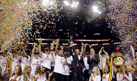 Cynthia Cooper Southern California head coach Cynthia Cooper, center, holds the trophy as she stands with her team on an award podium after they beat Oregon State to win the Pac-12 NCAA college championship basketball game, in Seattle. USC won 71-62
