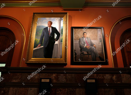 Portraits of former New York governors George Pataki, left, and David Paterson hang in the Hall of Governors at the state Capitol, in Albany, N.Y